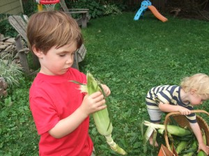 Connor and Ian shucking corn, July 2010